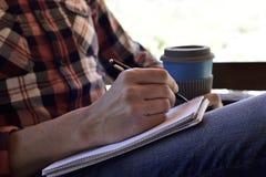Νεαρός άνδρας που γράφει σε ένα σημειωματάριο στοκ εικόνα με δικαίωμα ελεύθερης χρήσης