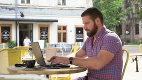 Νεαρός άνδρας που γράφει στο lap-top στον καφέ, βλασταημένο ολισθαίνων ρυθμιστής δικαίωμα φιλμ μικρού μήκους