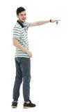 Νεαρός άνδρας που δείχνει σε κάτι με το δάχτυλό του που απομονώνεται στο μόριο Στοκ εικόνες με δικαίωμα ελεύθερης χρήσης