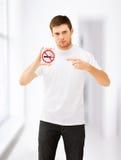 Νεαρός άνδρας που δείχνει στο σημάδι απαγόρευσης του καπνίσματος Στοκ Εικόνα