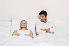 0 νεαρός άνδρας που εξετάζει τον ύπνο γυναικών στο κρεβάτι Στοκ Εικόνες