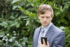Νεαρός άνδρας που εξετάζει το κινητό τηλέφωνο Στοκ Φωτογραφία