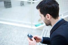 Νεαρός άνδρας που εξετάζει το κινητό τηλέφωνο Στοκ Φωτογραφίες
