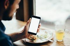 Νεαρός άνδρας που εξετάζει το τηλέφωνο, που κάθεται στο εστιατόριο Στοκ φωτογραφίες με δικαίωμα ελεύθερης χρήσης