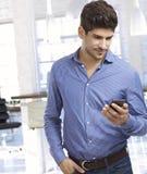 Νεαρός άνδρας που εξετάζει το smartphone Στοκ Φωτογραφία