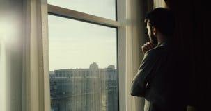 Νεαρός άνδρας που εξετάζει BT το παράθυρο την πόλη, σε αργή κίνηση 4K απόθεμα βίντεο