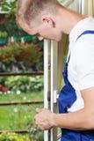 Νεαρός άνδρας που επισκευάζει ένα παράθυρο Στοκ εικόνες με δικαίωμα ελεύθερης χρήσης