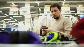 Νεαρός άνδρας που επιλέγει τα γυαλιά σνόουμπορντ στην υπεραγορά απόθεμα βίντεο