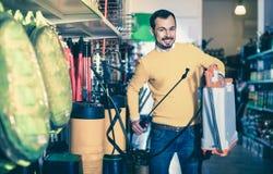 Νεαρός άνδρας που επιλέγει τον ψεκαστήρα κήπων στο κατάστημα εξοπλισμού κήπων Στοκ Φωτογραφία