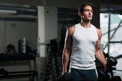 Νεαρός άνδρας που επιλύει με έναν αλτήρα στη γυμναστική Στοκ Εικόνα