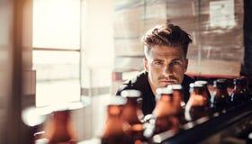 Νεαρός άνδρας που εποπτεύει τη διαδικασία της εμφιάλωσης μπύρας Στοκ εικόνα με δικαίωμα ελεύθερης χρήσης