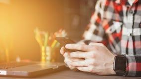 Νεαρός άνδρας που εργάζεται από το σπίτι που χρησιμοποιεί το έξυπνους τηλέφωνο και το φορητό υπολογιστή φιλμ μικρού μήκους