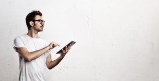 Νεαρός άνδρας που εργάζεται με την ψηφιακή ταμπλέτα Στοκ φωτογραφία με δικαίωμα ελεύθερης χρήσης