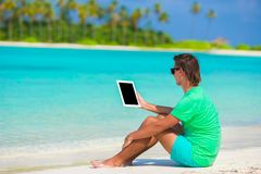 Νεαρός άνδρας που εργάζεται με το lap-top στην τροπική παραλία Στοκ Φωτογραφίες