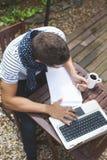 Νεαρός άνδρας που εργάζεται με το lap-top υπαίθρια Στοκ Εικόνες