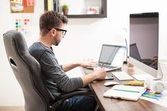 Νεαρός άνδρας που εργάζεται με δύο υπολογιστές Στοκ φωτογραφία με δικαίωμα ελεύθερης χρήσης
