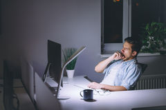 Νεαρός άνδρας που εργάζεται στον υπολογιστή τη νύχτα στο σκοτεινό γραφείο Στοκ φωτογραφίες με δικαίωμα ελεύθερης χρήσης
