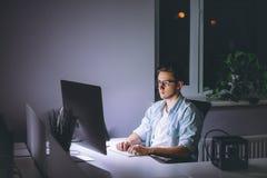 Νεαρός άνδρας που εργάζεται στον υπολογιστή τη νύχτα στο σκοτεινό γραφείο Στοκ εικόνα με δικαίωμα ελεύθερης χρήσης