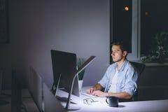 Νεαρός άνδρας που εργάζεται στον υπολογιστή τη νύχτα στο σκοτεινό γραφείο Στοκ Φωτογραφία
