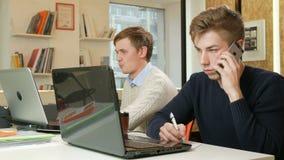 Νεαρός άνδρας που εργάζεται στο γραφείο των lap-top στο πρόγραμμα Κάποιος καλεί το τηλέφωνο στον πελάτη και τα αρχεία φιλμ μικρού μήκους