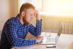 Νεαρός άνδρας που εργάζεται στο lap-top στο σπίτι Στοκ Εικόνες