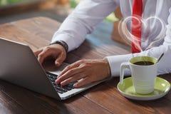 Νεαρός άνδρας που εργάζεται στο lap-top του σε μια καφετερία Στοκ φωτογραφία με δικαίωμα ελεύθερης χρήσης