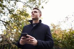 Νεαρός άνδρας που ελέγχει τα μηνύματα στο κινητό τηλέφωνο στην οδό της Οξφόρδης Στοκ φωτογραφίες με δικαίωμα ελεύθερης χρήσης