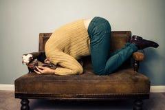 Νεαρός άνδρας που θάβει το πρόσωπό του στον παλαιό καναπέ Στοκ εικόνα με δικαίωμα ελεύθερης χρήσης