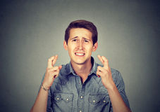 Νεαρός άνδρας που κάνει μια επιθυμία που κρατά τα δάχτυλά του διασχισμένα Στοκ εικόνες με δικαίωμα ελεύθερης χρήσης