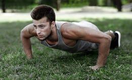 Νεαρός άνδρας που κάνει την ώθηση UPS στη χλόη στο θερινό πάρκο στοκ φωτογραφία