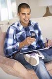 Νεαρός άνδρας που κάνει τη γραφική εργασία και που χρησιμοποιεί το κινητό τηλέφωνο στο σπίτι Στοκ εικόνα με δικαίωμα ελεύθερης χρήσης