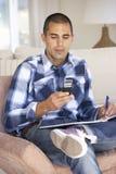 Νεαρός άνδρας που κάνει τη γραφική εργασία και που χρησιμοποιεί το κινητό τηλέφωνο στο σπίτι Στοκ Εικόνες