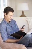 Νεαρός άνδρας που κάνει τη γραφική εργασία και που χρησιμοποιεί το κινητό τηλέφωνο στο σπίτι Στοκ Φωτογραφίες