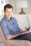 Νεαρός άνδρας που κάνει τη γραφική εργασία και που χρησιμοποιεί το κινητό τηλέφωνο στο σπίτι Στοκ φωτογραφίες με δικαίωμα ελεύθερης χρήσης