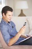 Νεαρός άνδρας που κάνει τη γραφική εργασία και που χρησιμοποιεί το κινητό τηλέφωνο στο σπίτι Στοκ φωτογραφία με δικαίωμα ελεύθερης χρήσης