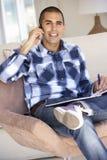 Νεαρός άνδρας που κάνει τη γραφική εργασία και που χρησιμοποιεί το κινητό τηλέφωνο στο σπίτι Στοκ Φωτογραφία