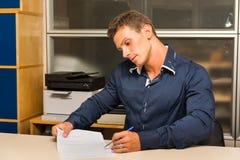 Νεαρός άνδρας που κάνει τη γραφική εργασία στο γραφείο γραφείων, παρουσίαση Στοκ φωτογραφία με δικαίωμα ελεύθερης χρήσης