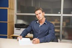 Νεαρός άνδρας που κάνει τη γραφική εργασία στο γραφείο γραφείων, γράψιμο Στοκ φωτογραφίες με δικαίωμα ελεύθερης χρήσης
