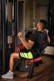Νεαρός άνδρας που κάνει pull-down LATS workout Στοκ Εικόνες