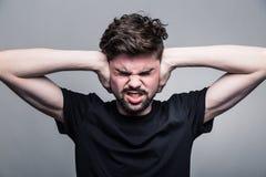 Νεαρός άνδρας που καλύπτει τα χέρια αυτιών του Στοκ φωτογραφία με δικαίωμα ελεύθερης χρήσης
