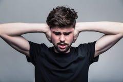 Νεαρός άνδρας που καλύπτει τα χέρια αυτιών του Στοκ φωτογραφίες με δικαίωμα ελεύθερης χρήσης