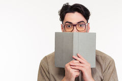 Νεαρός άνδρας που καλύπτει το πρόσωπό του με το βιβλίο στοκ φωτογραφία