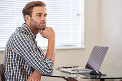 Νεαρός άνδρας που κοιτάζει σκεπτικά στην απόσταση, που χρονοτριβεί την εργασία του Στοκ Εικόνα