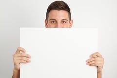 Νεαρός άνδρας που κρατά έναν λευκό πίνακα Στοκ Φωτογραφίες