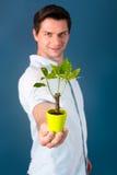 Νεαρός άνδρας που κρατά ένα μικρό δέντρο Στοκ Εικόνες