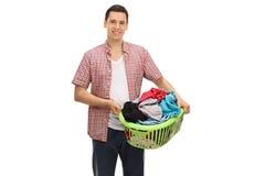 Νεαρός άνδρας που κρατά ένα σύνολο καλαθιών πλυντηρίων των ενδυμάτων Στοκ εικόνα με δικαίωμα ελεύθερης χρήσης