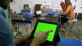 Νεαρός άνδρας που κρατά ένα PC ταμπλετών διαθέσιμο καθμένος σε ένα γραφείο φιλμ μικρού μήκους