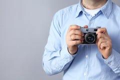 Νεαρός άνδρας που κρατά μια κάμερα, που απομονώνεται στο γκρίζο υπόβαθρο Στοκ φωτογραφία με δικαίωμα ελεύθερης χρήσης