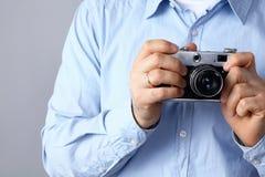 Νεαρός άνδρας που κρατά μια κάμερα, που απομονώνεται στο γκρίζο υπόβαθρο Στοκ Εικόνες
