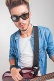 Νεαρός άνδρας που κρατά μια κιθάρα εξετάζοντας τη κάμερα Στοκ εικόνες με δικαίωμα ελεύθερης χρήσης